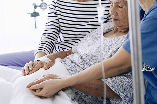 elderly female patient in hospital holding hands with loved ones